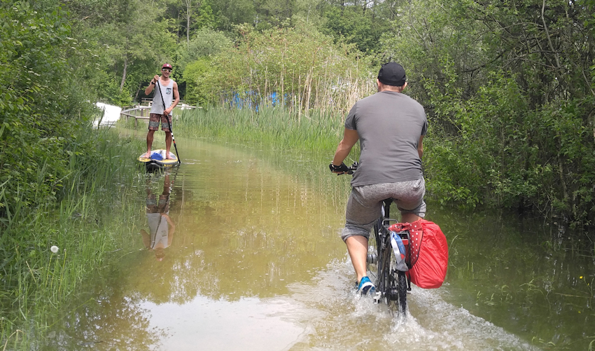 skurile Begegnung Fahrrad und Standup Paddler Chiemsee